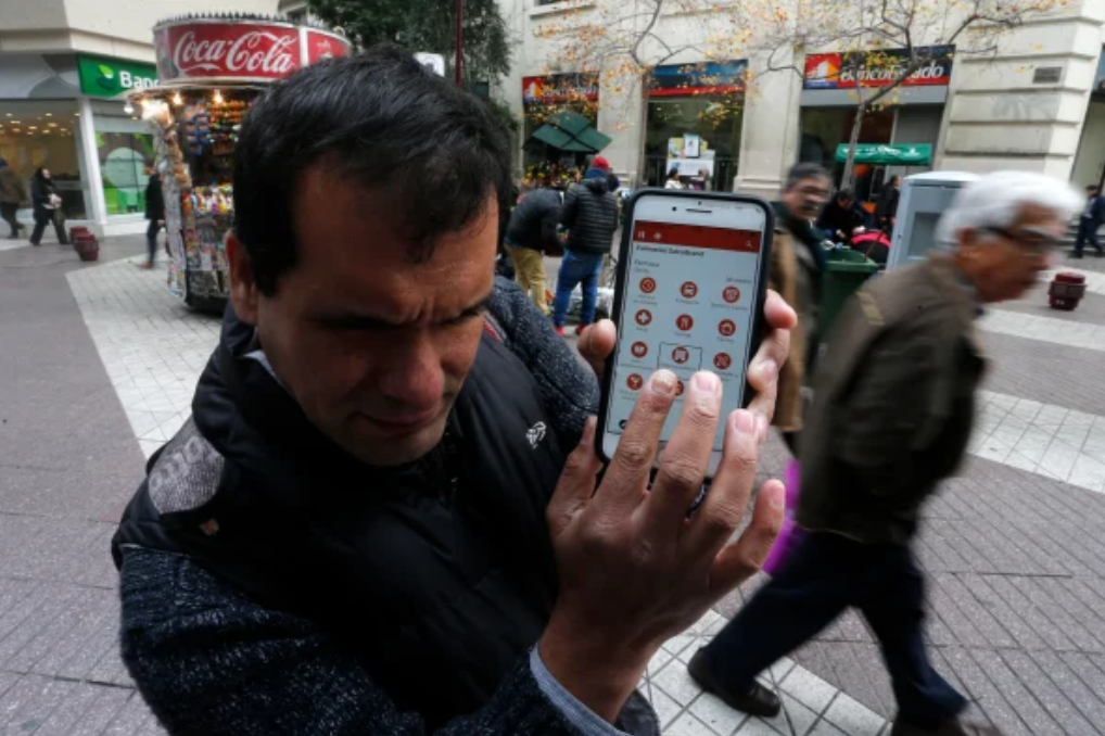 A man uses the Lazarillo app in a crowded plaza