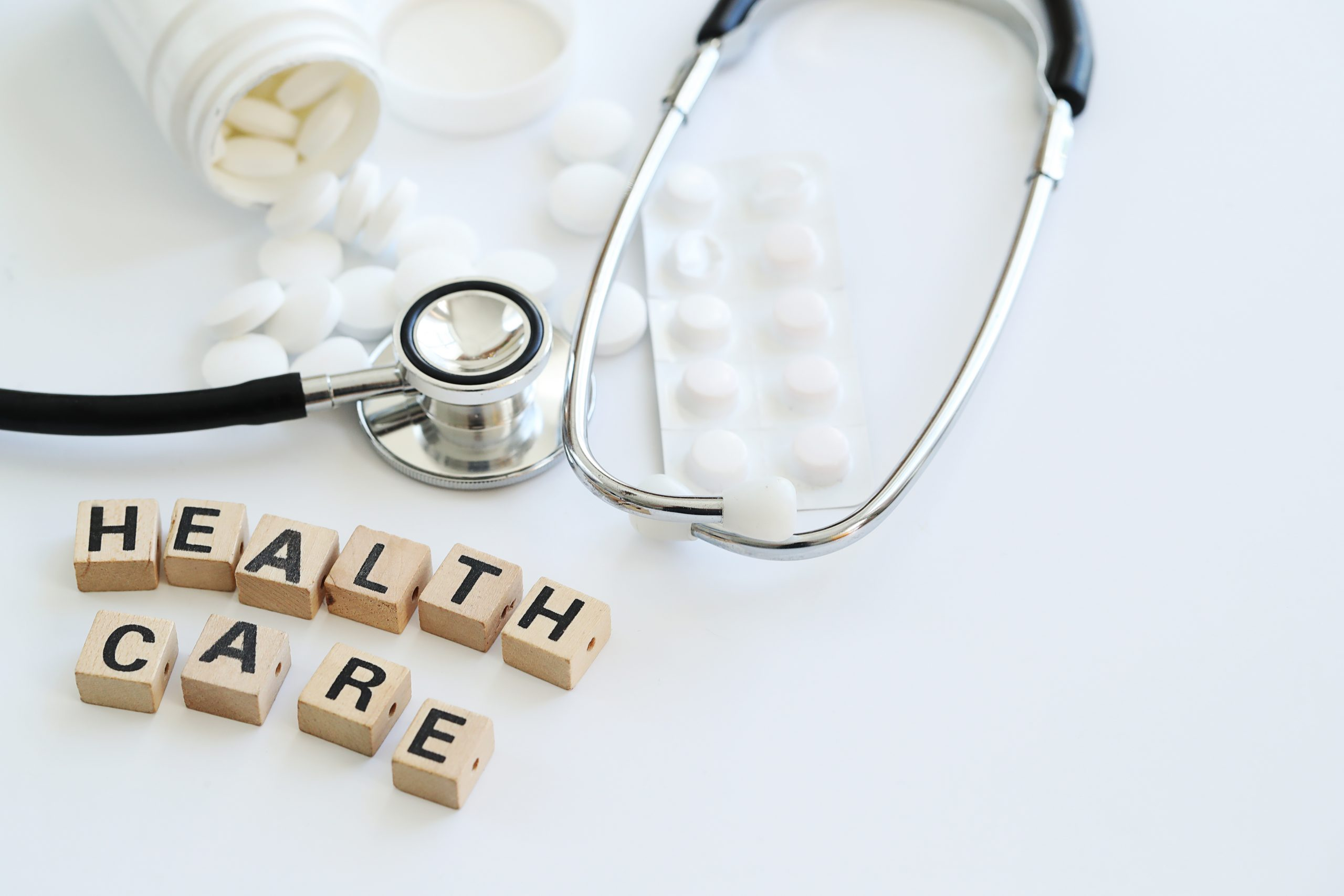 """The words """"health care"""" are spelled out in scrabble letters on a table next to a stethescope and pill bottle."""
